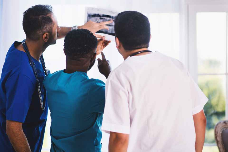 three person looking at x ray result